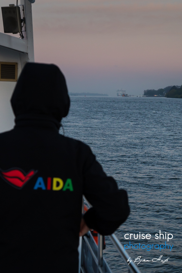 Die AIDAprima beim Erstanlauf auf der Elbe mit AIDA Mitarbeiter und AIDA Logo
