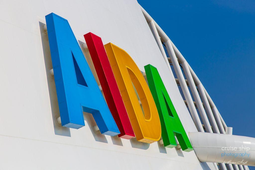 Die bunten Buchstaben des AIDA Logos bei Sonnenschein